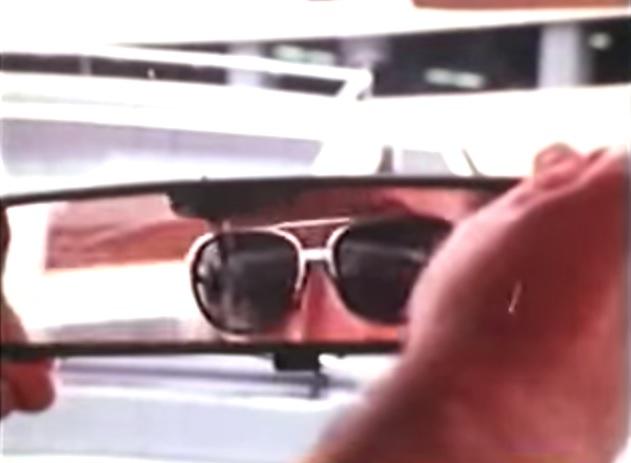 Reyner Banham adjusting his rear-view mirror.