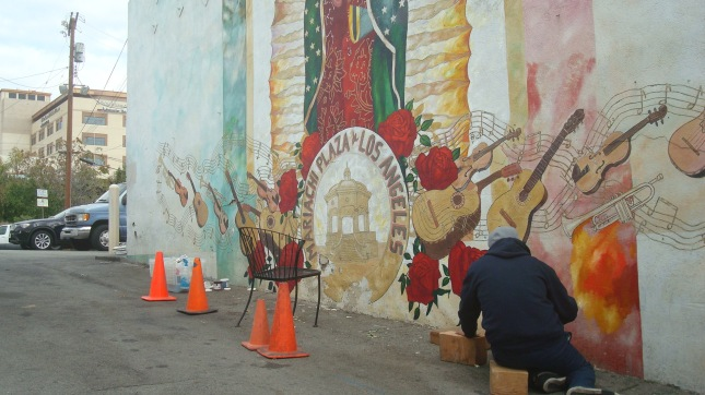 Artist working on a mural just off the plaza.