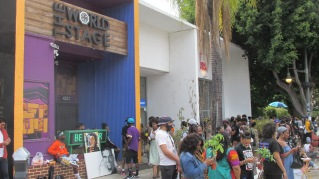 People hanging out in front of Leimert Park landmark The World Stage.